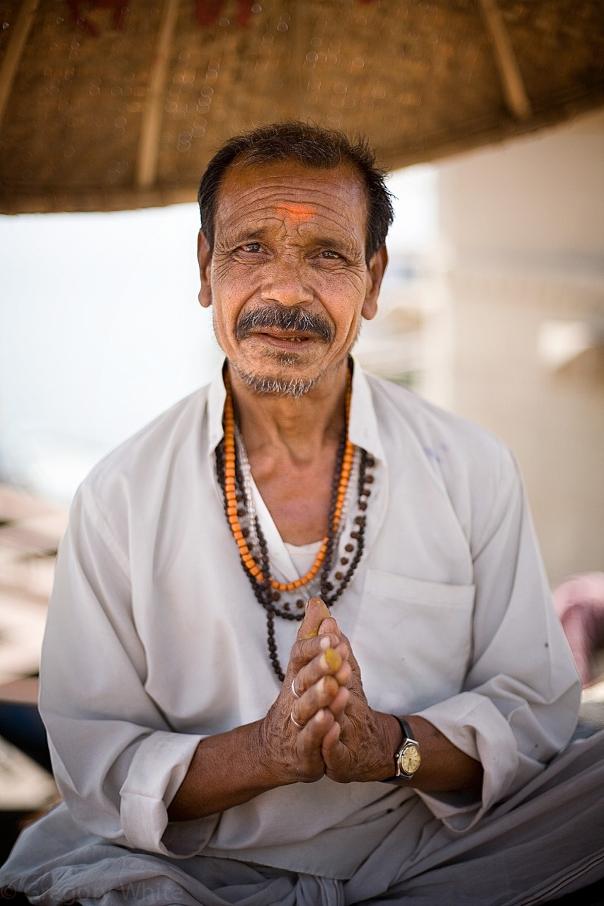 A guru sits on the shores of the Ganges and offers prayers and offerings in your name...
