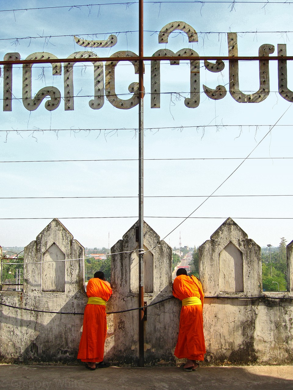 Monks take in the view from the towering concrete national monument in Vientiene, Laos.