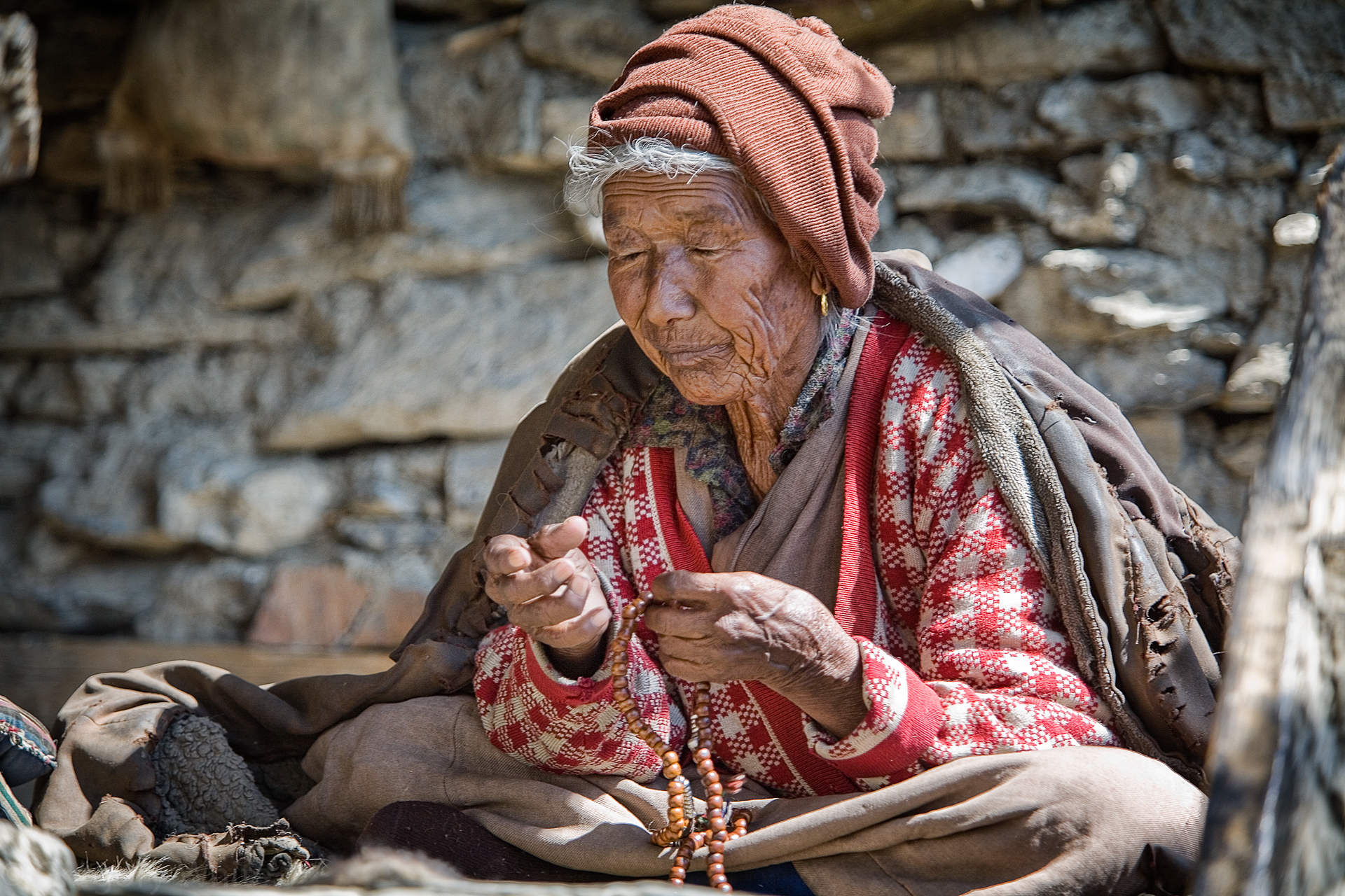 Lama's blind wife prays with beads.